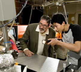Richard Zare, the Marguerite Blake Wilbur Professor in Natural Science, and postdoctoral researcher Jianyang Zhang peer into the recesses of the vacuum chamber where the team's experiments discovered that near misses of hydrogen atoms and deuterium molecules produce an unexpected transfer of energy. (Linda A. Cicero, Stanford News Service)