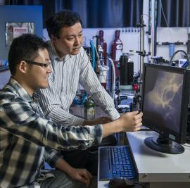 Graduate student Guosong Hong and chemistry professor Hongjie Dai look at the vascular structures in a mouse model of peripheral arterial disease with blood vessels shown in great detail using near-infrared II (NIR-II) fluorescence imaging. The technique, developed by the Dai research group in collaboration with the John Cooke group from the Stanford School of Medicine, allows them to see the small biological structures deep inside a body with high clarity. (Linda Cicero, Stanford News Service)